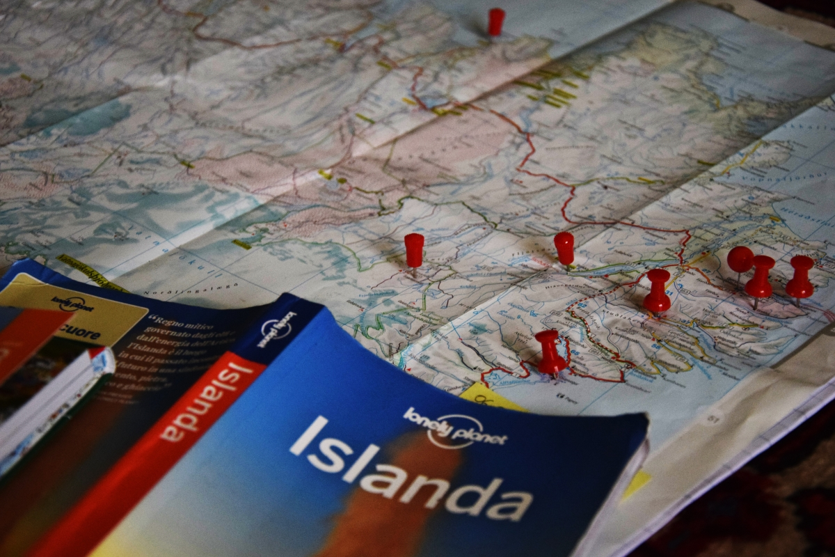 Picture taken by The Half Hermit while planning the itinerary of #destinationIceland: the book cover of the Lonely Planet travel guide and a map of Iceland with pins in places he wants to visit.