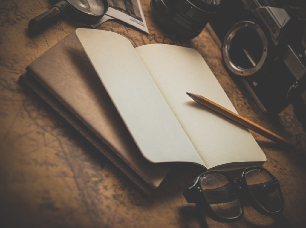 Un taccuino e una matita, poggiati su una carta geografica e circondati da occhiali, macchina fotografica, polaroid e lente d