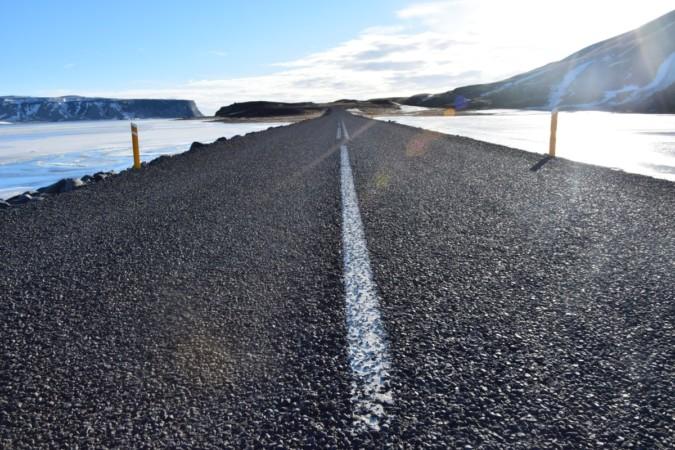"""Fotografia scattata da The Half Hermit con inquadratura filo terra della strada che conduce a Dyrhólaey, promontorio sulla costa meridionale dell'Islanda. L'immagine rappresenta il motto di The Half Hermit """"Il mio luogo è il movimento""""."""