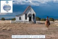 Fotografia di un cowboy di spalle che si avvicina a cavallo a una vecchia e piccola chiesa in legno: con il senno di poi #destinationIceland sembra una passeggiata nel giardino sotto casa con i preparativi vissuti fingendo di essere un cowboy alla conquista del west.