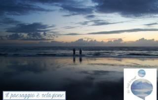 Fotografia che ritrae due uomini di spalle in riva al mare mentre contemplano l'alba: sono immersi nel paesaggio, vivono la relazione con esso.